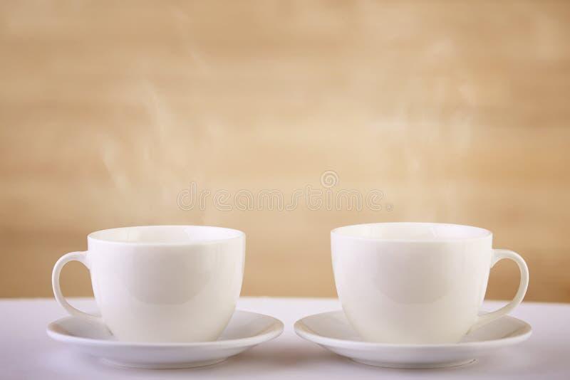 Två vita porslintekoppar på den vita tabellen visar fullständigt och idéer för den enkla designen, selektiv fokus royaltyfri fotografi
