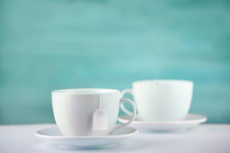 Två vita porslintekoppar på den vita tabellen visar fullständigt och idéer för den enkla designen, selektiv fokus royaltyfria bilder