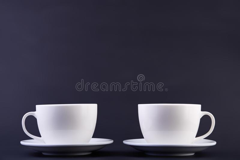 Två vita porslintekoppar på mörk bakgrund visar fullständigt och idéer för den enkla designen arkivfoton