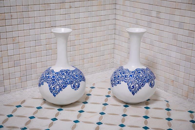 Två vita vaser med blåa modeller som står på en beige kvast med blålinjen på bakgrunden av en vägg av beigamarmortegelplattor in arkivbilder