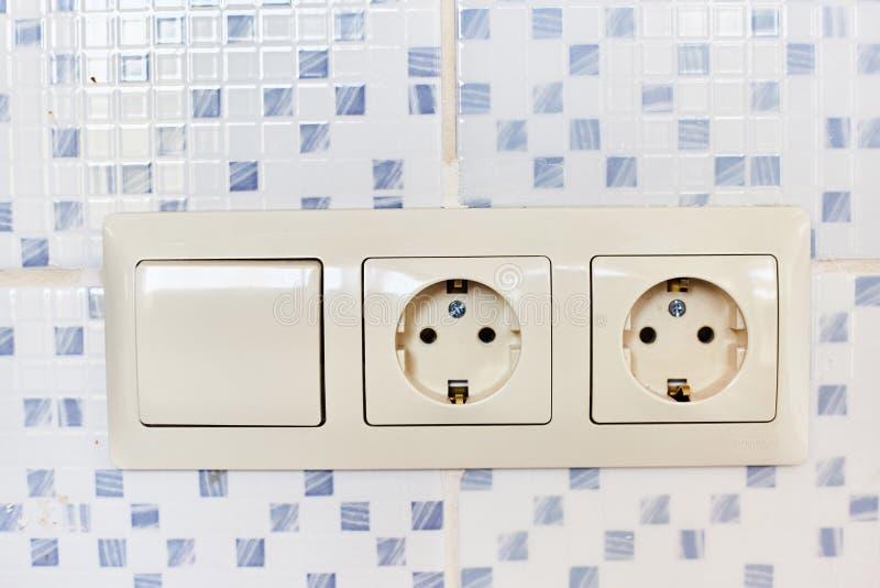 Två vita 220 volt uttag med en strömbrytare royaltyfria foton