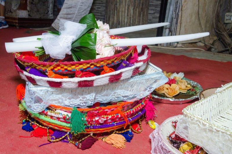 Två vitbröllopstearinljus följe och korgar av godisen i den orientaliska stilen på festivalhinaen royaltyfri foto