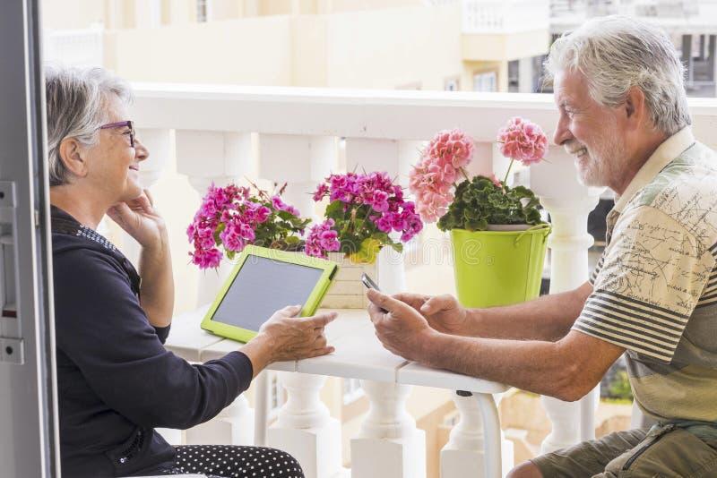Två vuxen människapersoner använder mobila den utomhus- teknologiinternet i den hem- terrassen royaltyfri fotografi