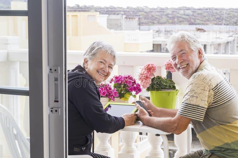 Två vuxen människapersoner använder mobila den utomhus- teknologiinternet i den hem- terrassen arkivbild