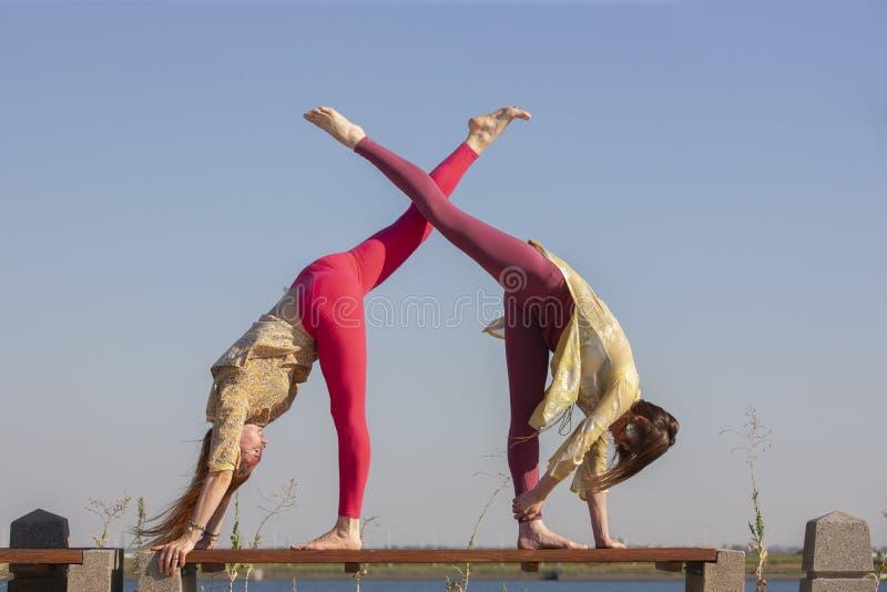 Två vuxna kvinnor åldrades yoga i sommar i parkerar utomhus royaltyfri foto