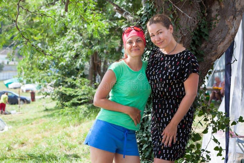 Två vuxna kvinnor som tillsammans står i campa område på sommarsemestrar royaltyfri bild