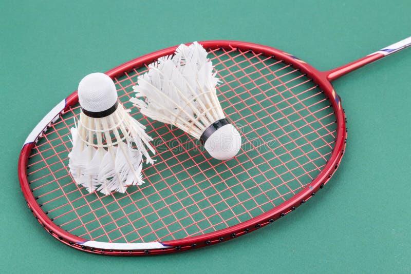 Två worned ut badmintonfjäderboll med racket på den gröna domstolen fotografering för bildbyråer