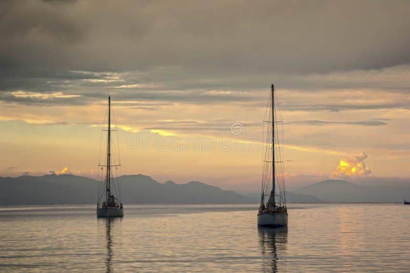 Två yachter skriver in Rhodes port på solnedgången arkivfoto