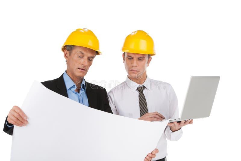 Två yrkesmässiga byggmästare som ser plan. arkivfoto