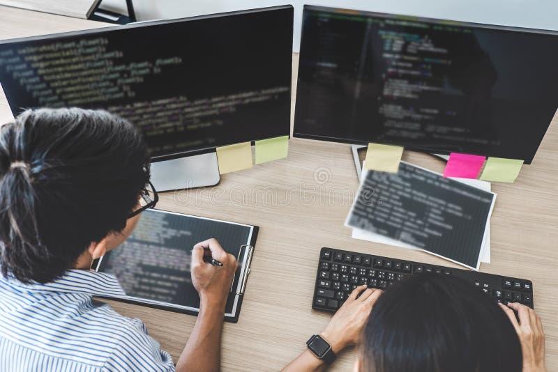 Två yrkesmässiga programmerare som samarbetar på den framkallande programmien arkivbild
