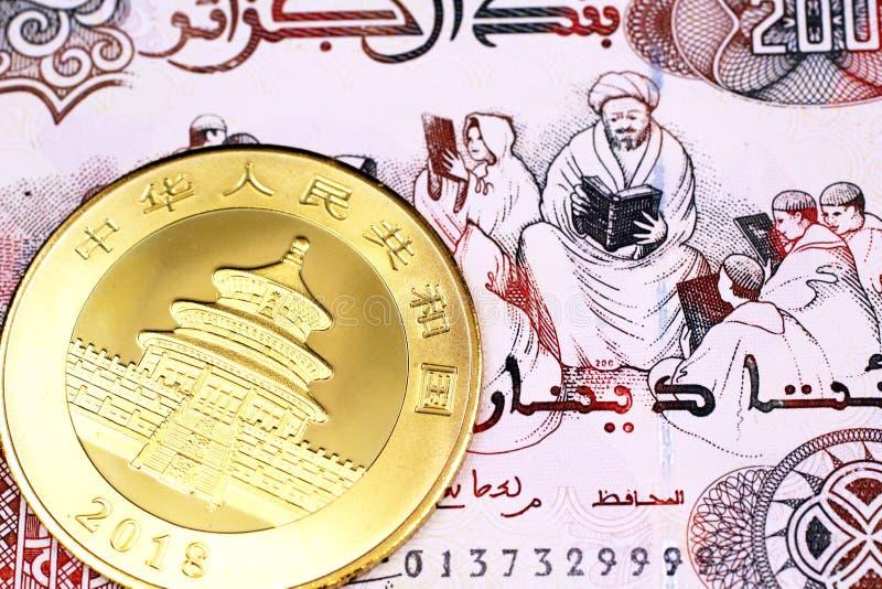 Tvåhundra algeriska dinar stänger sig upp med ett guld- mynt från Kina royaltyfria bilder