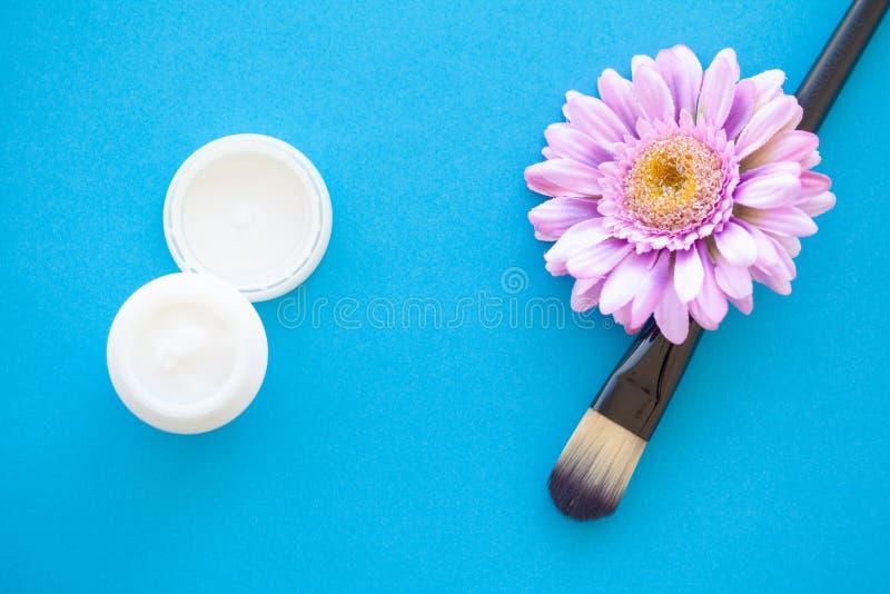 Tvål-, handduk- och blommasnowdrops Ansiktsbehandlingmaskeringar med naturliga ingredienser på blåa Backg arkivfoton