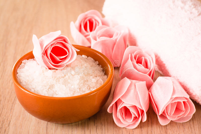 Tvål i form av blommor, hav som är salt i en bunke, och en handduk på en träbakgrund arkivfoton