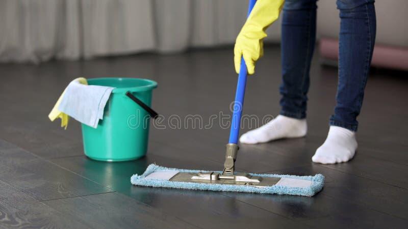 Tvångsmässigt med den unga damen för renlighet som tvättar grundligt golvet av hennes hus fotografering för bildbyråer