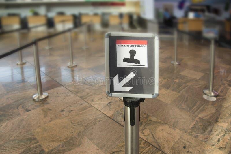 Tvåspråkigt tullkontrolltecken på den internationella flygplatsen royaltyfri fotografi