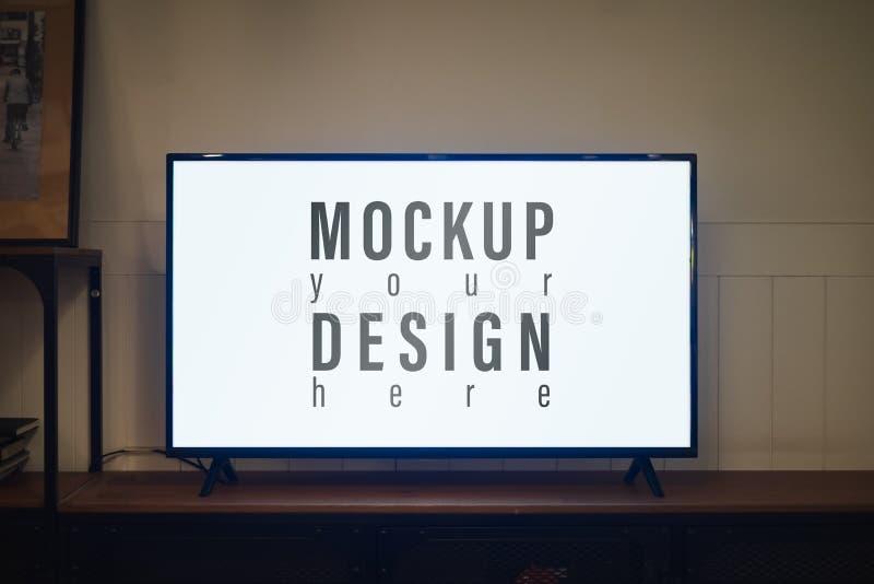 TV με το κενό γραφείο οθόνης και ραφιών τη νύχτα contemporaly στο καθιστικό, TV των κενών οδηγήσεων οθόνης προτύπων για τη διαφήμ στοκ φωτογραφία