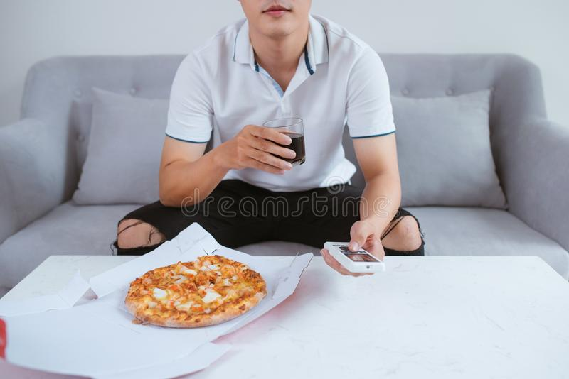 TV ρολογιών ατόμων και κατανάλωση της πίτσας με το μη αλκοολούχο ποτό κλείστε επάνω Συνεδρίαση στοκ εικόνες με δικαίωμα ελεύθερης χρήσης