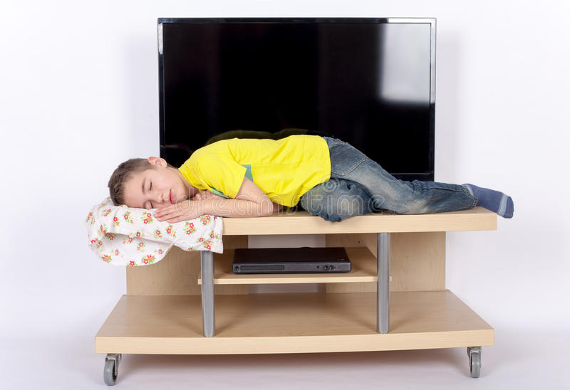 Tv addiction. Concept - Small boy sleeping in front of the TV stock photo