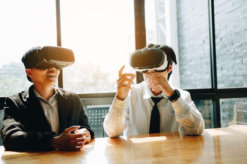 Tv? aff?rsaff?rspersoner med virtuell verkligheth?rlurar med mikrofon i kontoret arkivbilder
