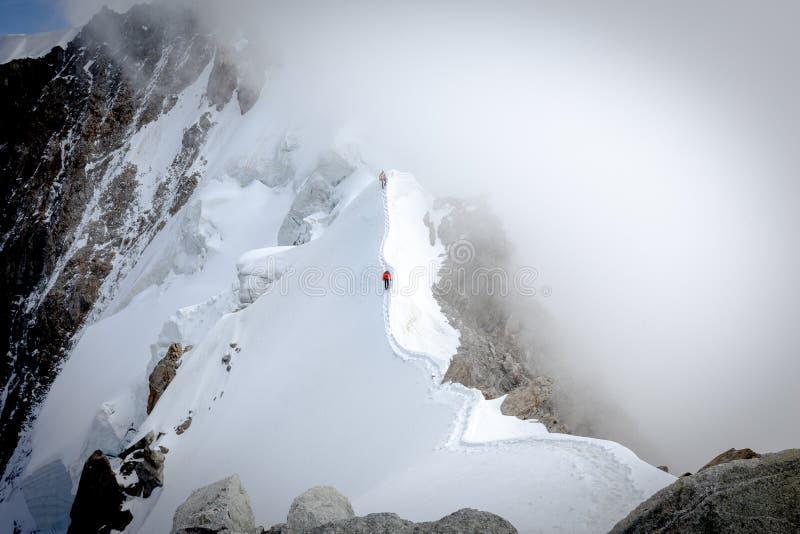 Tv? alpinister som g?r den tunna bergkanten arkivbild