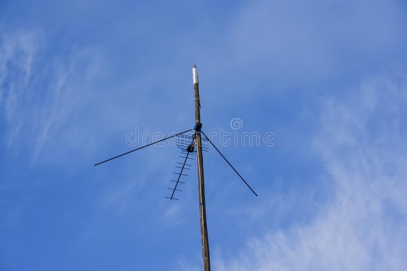 TV antenna attached to a wooden pole. Against the blue sky royalty free stock images