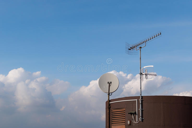 TV antenna and satelite dish mounted on roof. Against blue sky with clouds stock photography
