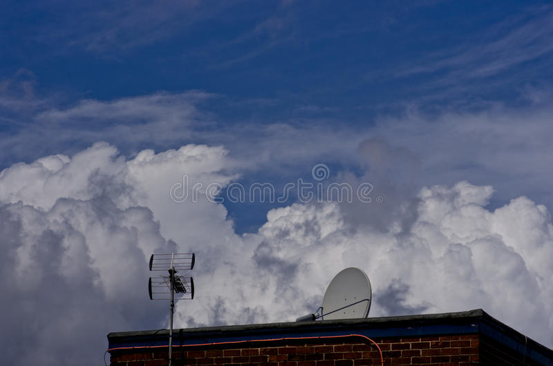 TV antenna, satellite dish on blue cloudy sky background. stock image