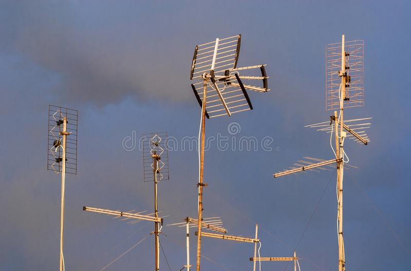 TV antennas with clouds. Different kinds of TV antennas and arrays against a cloudy sky royalty free stock photos