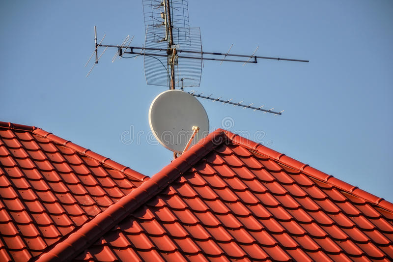 TV antennas and satellite dish for television mounted on the tiled roof of house isolated on blue sky background in countryside. Telecommunications aerials and royalty free stock images
