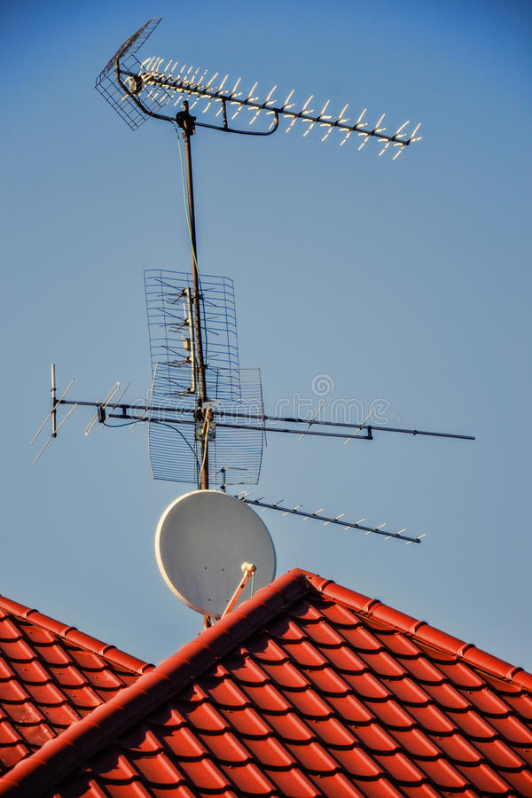 TV antennas and satellite dish for television mounted on the tiled roof of house isolated on blue sky background in countryside. Telecommunications aerials and royalty free stock image