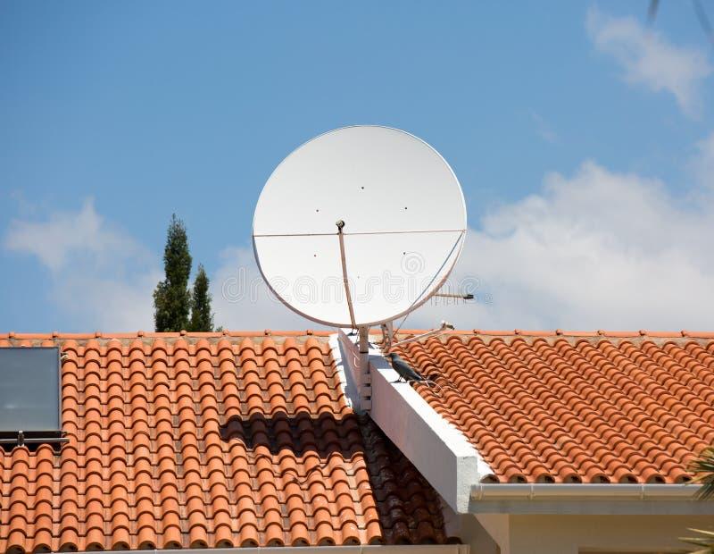 TV-antenne op het rode tegeldak stock fotografie