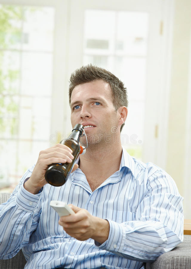 TV and beer. Man watching TV at home, sitting on couch, holding remote control in hand, drinking beer royalty free stock photography