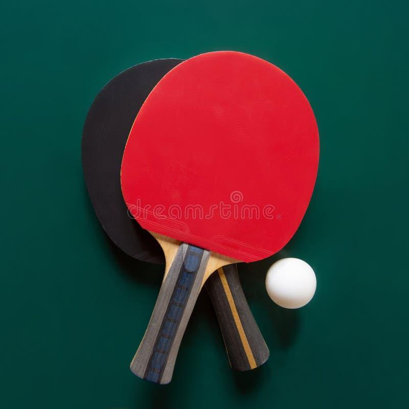 Tv? bordtennisracket och en boll p? en gr?n tabell C arkivfoto