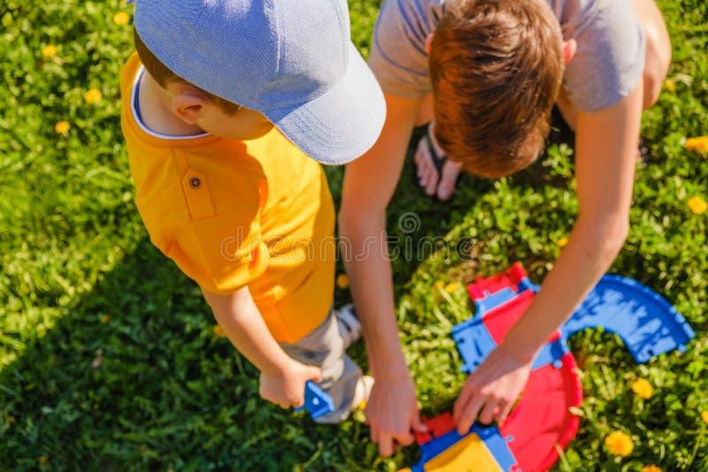 Tv? broderlekar med en leksakbil p? gr?smattan f?r gr?nt gr?s royaltyfri fotografi