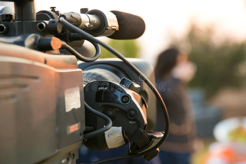 TV Camera and presenter host on a live news broadcast on location. At sunrise stock photography