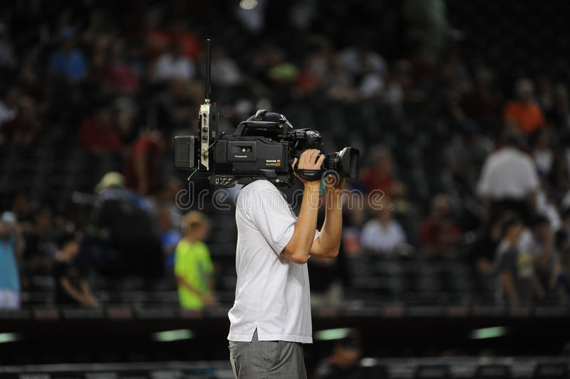 A TV cameraman shooting a Baseball game. Before the start of the game on the field stock photos