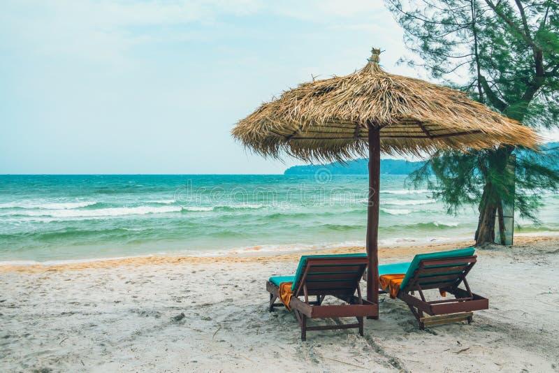 Tv? chaisevardagsrum och sugr?rparaply p? den tropiska stranden Kust av ön Koh Rong Samloem royaltyfri fotografi