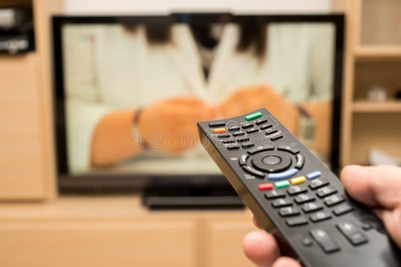 TV de observación y usar el control remoto moderno negro Dé la explotación agrícola TV teledirigida con una televisión en el fond imagenes de archivo
