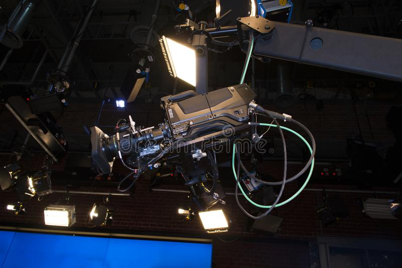 TV digital professional camera on crane shooting TV show. Spotlights in the background.  royalty free stock image