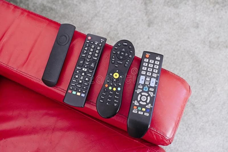 TV digital wireless remote controls on red sofa chair arm. Uk stock images
