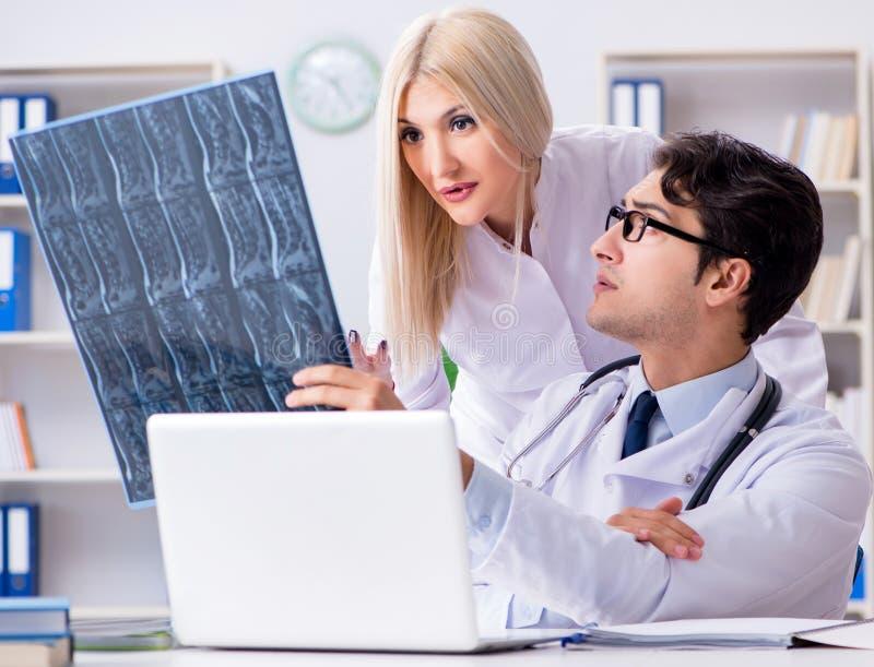 Tv? doktorer som unders?ker r?ntgenstr?lebilder av patienten f?r diagnos arkivfoton