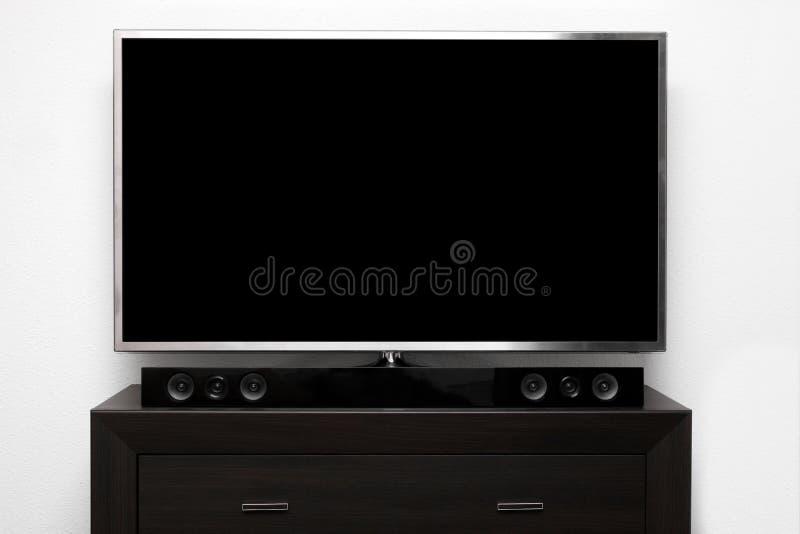 TV en blanco con el sistema estéreo en cómoda marrón imagen de archivo