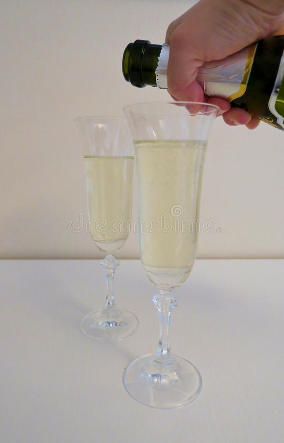 Tv? exponeringsglas av att moussera champagne p? en vit bakgrund arkivbilder