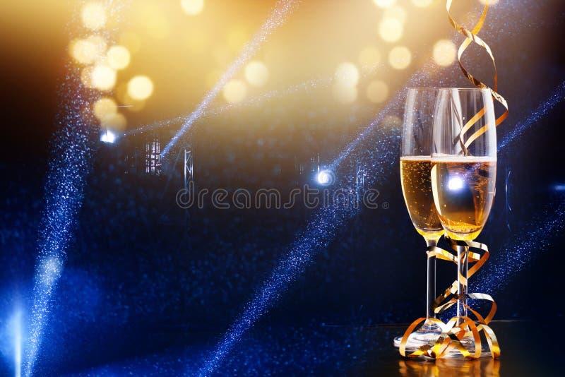 Tv? exponeringsglas av champagne i str?lkastaren - ber?m f?r nytt ?r royaltyfri bild