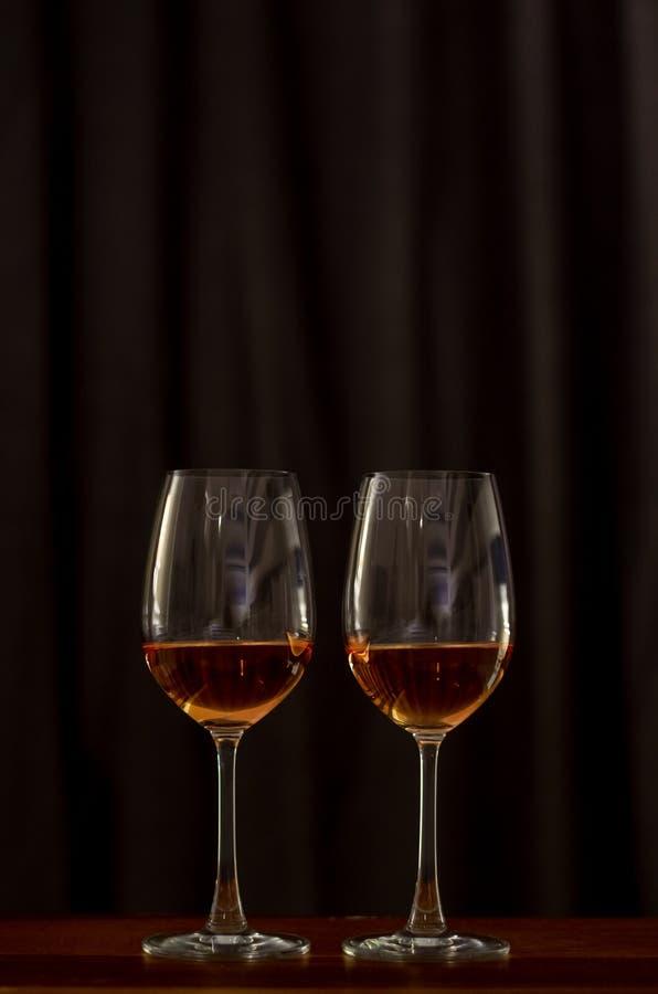 Tv? exponeringsglas av rosa vin p? tr?tabellen som firar f?r ett par arkivbild
