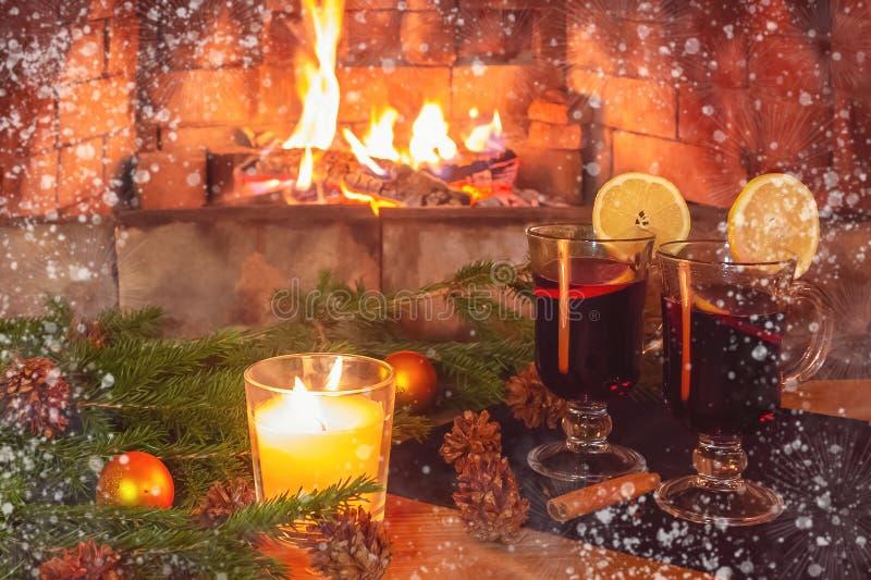 Tv? exponeringsglas med funderat vin, en stearinljus, granfilialer med garneringar p? en tr?tabell mot bakgrunden av a fotografering för bildbyråer