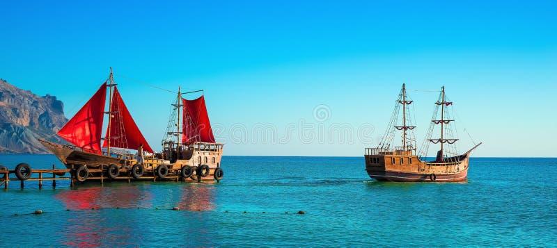 Tv? gamla tr?skepp Ett av dem med r?tt seglar ?r p? pir fotografering för bildbyråer
