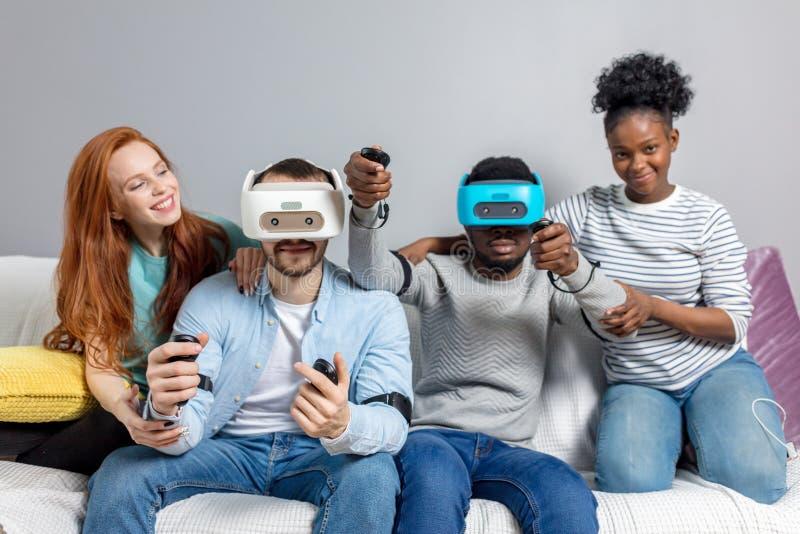 Tv? grabbar som spelar videospel genom att anv?nda VR-exponeringsglas och flickv?nner, st?ttar dem arkivbild