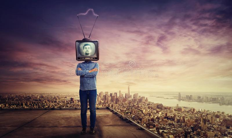 Tv head. Addicted man with crossed arms and old tv instead of head standing on skyscraper rooftop over big city sunset horizon. Television manipulation and royalty free stock images