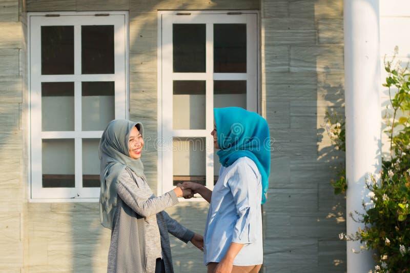 Tv? hijabkvinnagrannar att m?ta och s?ga hi stund som ler och att skaka h?nder framme av deras hus royaltyfri foto